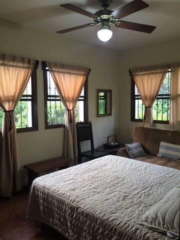 El cuarto, acogedor, muy fresco rodeado de 4 ventanales, y con abanico de techo. A/C portátil disponible.