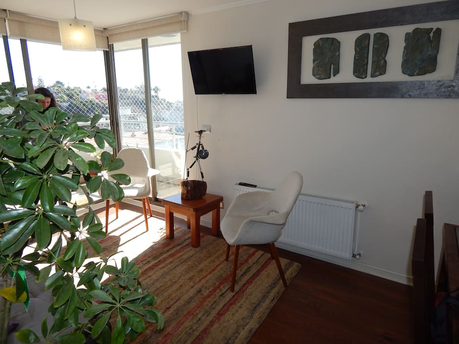 Otra vista de la sala de estar que incluye un televisor con canales de cable.