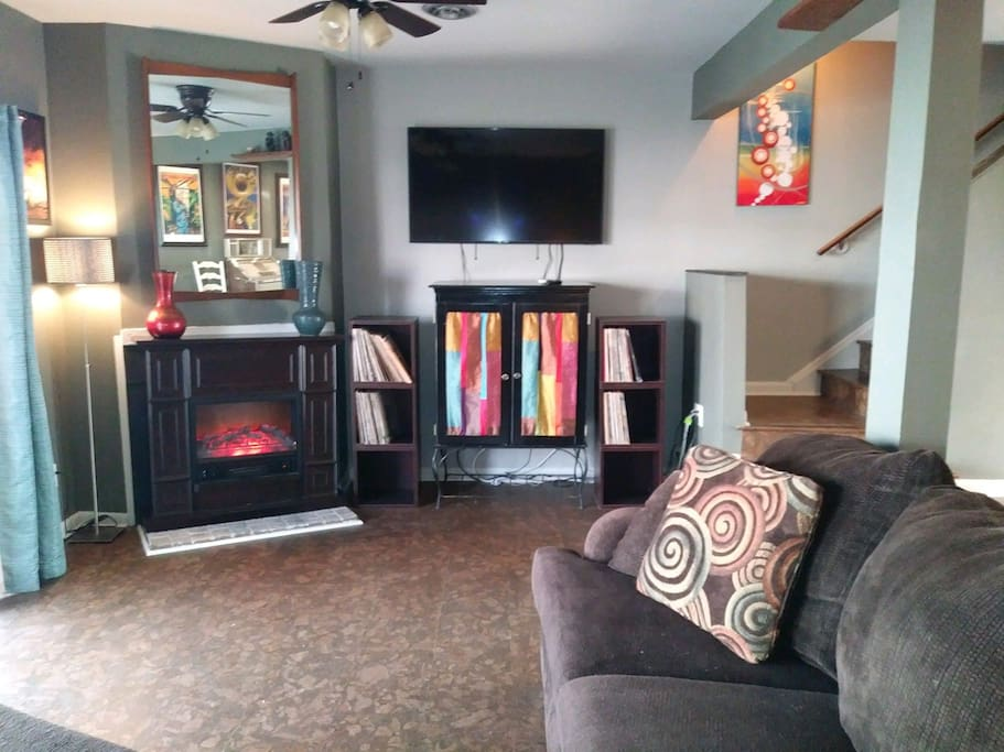 """Spacious living room with a 60"""" HDTV and space heating fire place overlooking the inlet out the back door."""