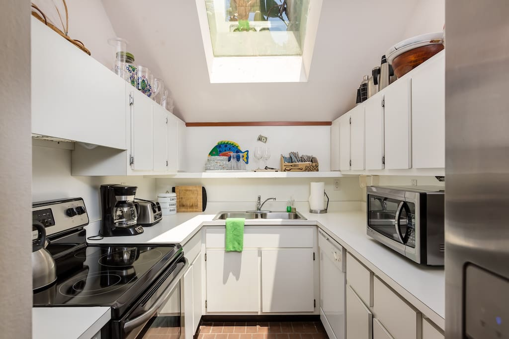 The fully equipped kitchen includes stainless steel appliances and a starter supply of dish soap and paper towels.