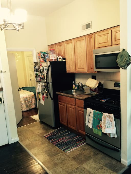 New kitchen with over, stove, refrigerator, freezer, stainless steel sink with garbage disposal