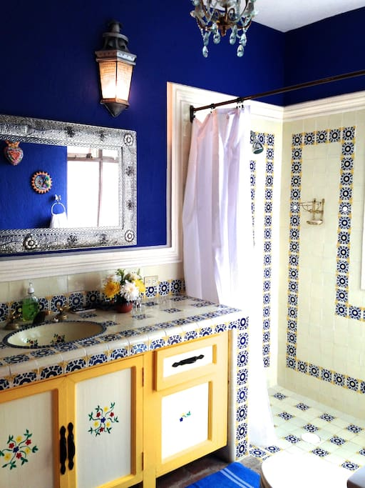 Cheerful and spacious bathroom with hand painted cabinets and pretty tiles