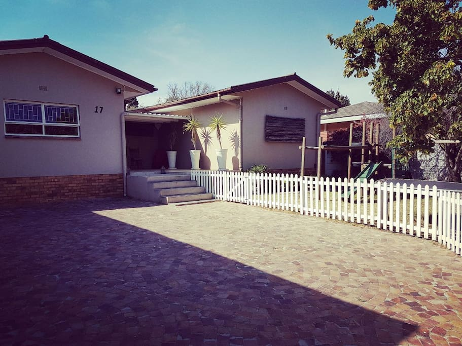 Spacious driveway with secure parking for vehicles behind electric gate. Also includes jungle gym and trampoline for kids.