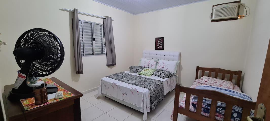 Quarto com uma cama de casal e uma cama de solteiro. Ar condicionado, ventilador, ferro de passar e cabides.