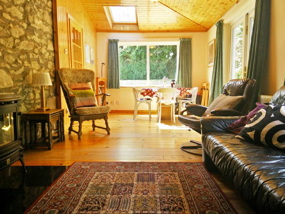 The Sunroom, for dining and relaxing. Features include high wood-panelled ceiling, wood burning stove and patio doors out to decking.