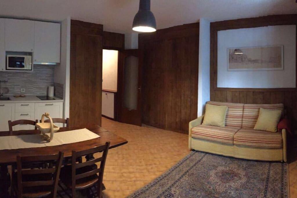 Zona living con divano letto. Cucina nuova e tavolo da 6 persone. Finiture di pregio