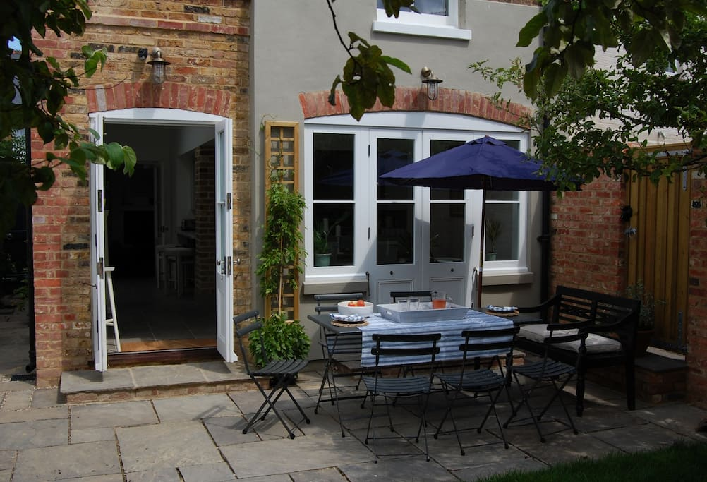 Patio dining area with tables and seating for 8 guests plus BBQ & parasol