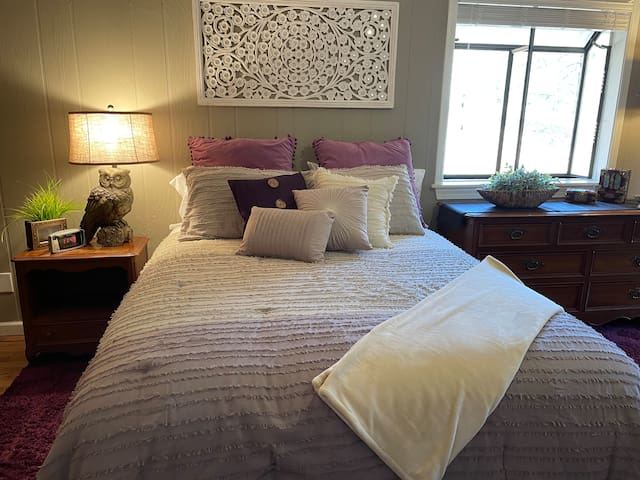 Queen size bed with dresser in sleeping area