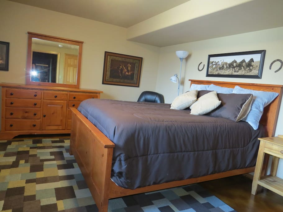 Sleep well on this comfortable queen-sized bed, surrounded by rodeo and horse images.