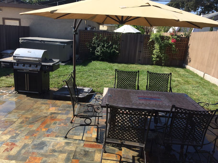 Backyard and patio with grill and hot tub.