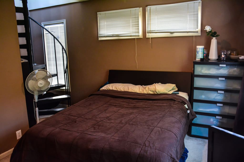 2nd floor bedroom with large queen sized bed and staircase to roofdeck