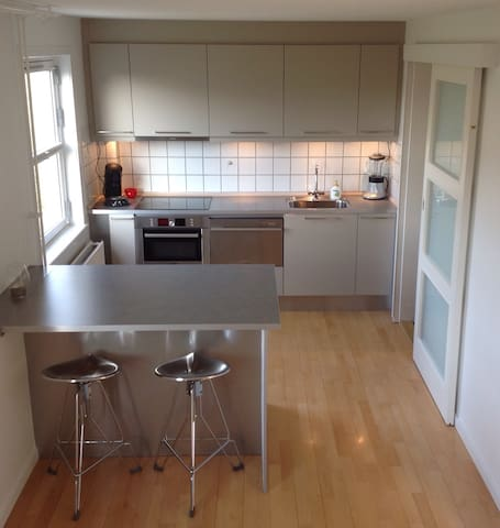 Modern kitchen, with all the tools to make a dinner for 2. Kitchen has dishwasher, fridge with little freezer.