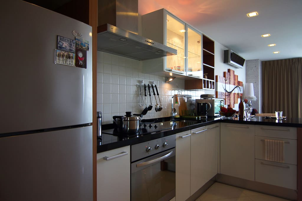 Western kitchen equipped with 4-ring electric hob and hood, oven, microwave, refrigerator, kettle and a toaster.