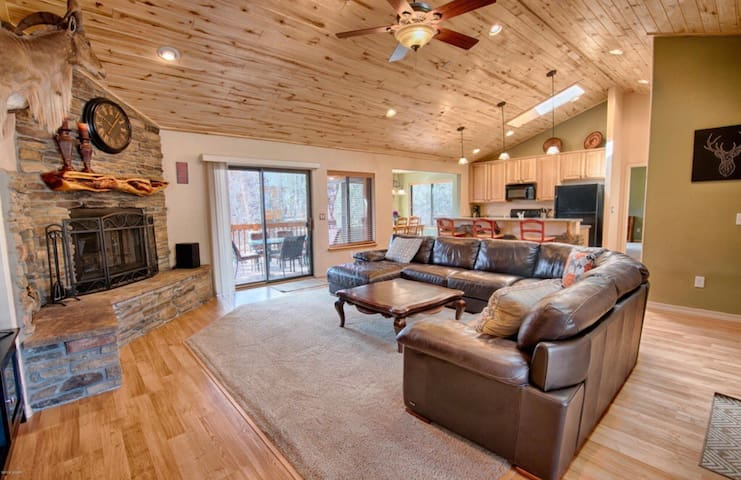 Family room with a gigantic leather sectional. Cozy fireplace and smart TV. With internet and Netflix.