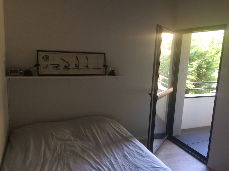 Chambre : accès au balcon et lit quen size