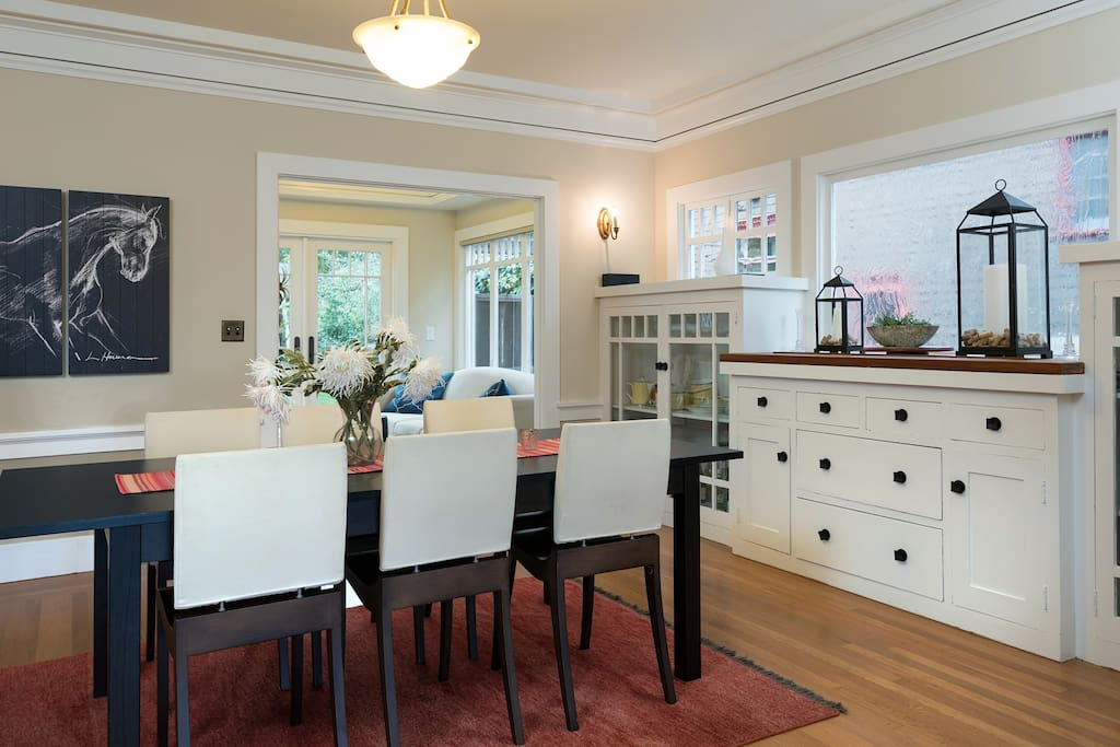 Beyond the living area is the formal dining area, also elegantly furnished and light-filled, with the kitchen in the background