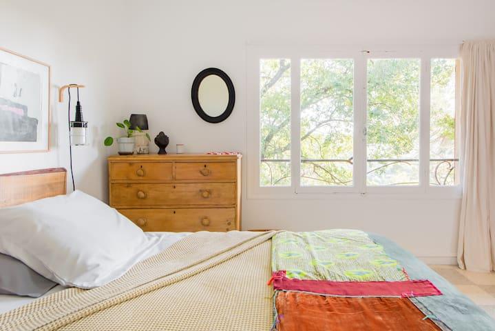 Chambre à coucher avec deux fenêtres donnant sur les arbres environnant.  Les levés de soleil sont de toute beauté vu du lit...