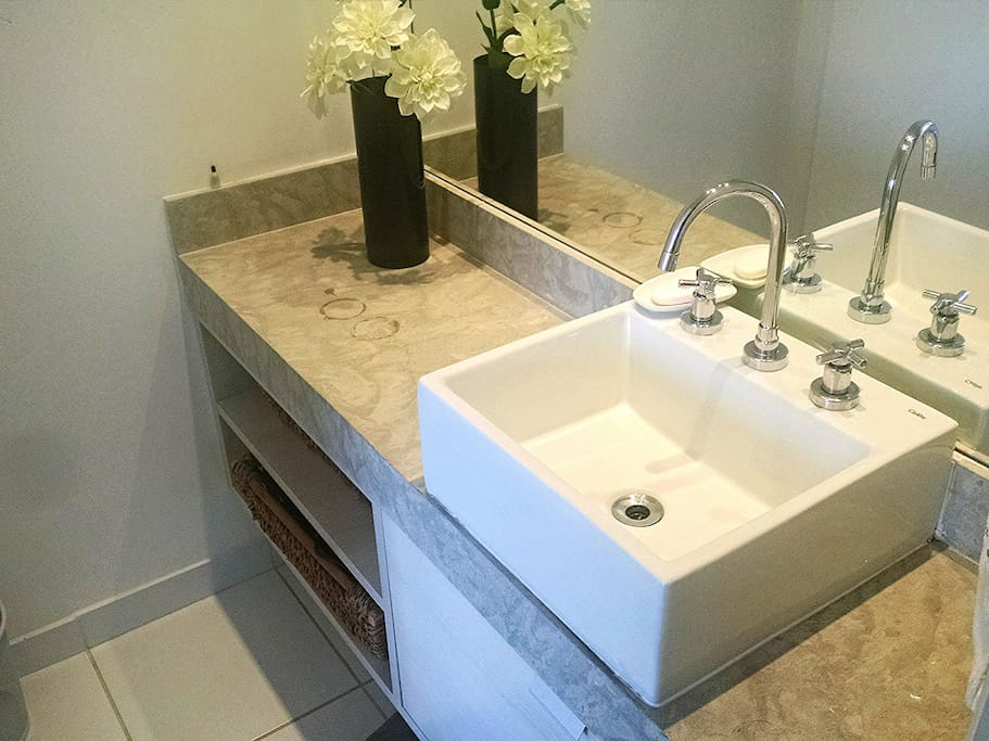 Banheiro do quarto de casal com porta de correr e separado do chuveiro e vaso