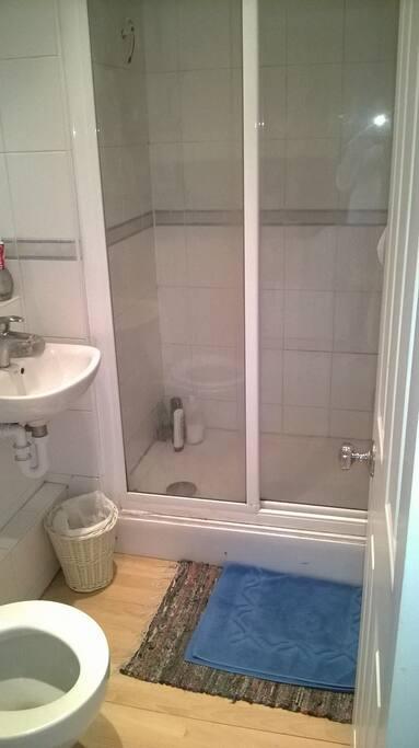 Hot water shower, heated towel rail, sink, toilet.