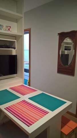 Sala com a mesa dobrável, podendo ser totalmente recolhida para dentro do móvel que divide a sala