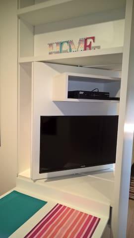 A TV pode ser vista do quarto ou da sala.