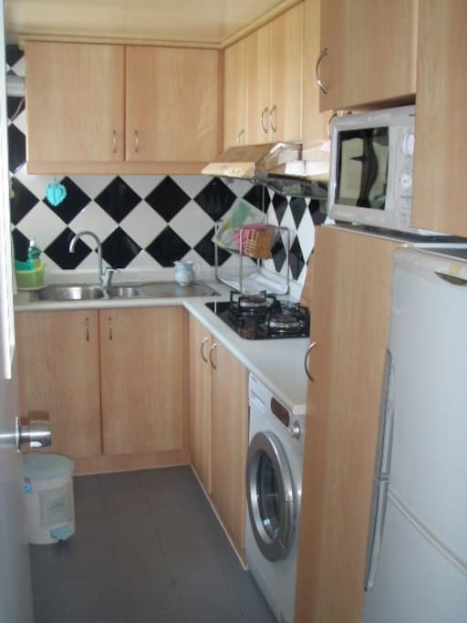 Kitchen with three-ring gas cooker, microwave, fridge and washing machine.  Also equipped with cookware, crockery and cutlery.