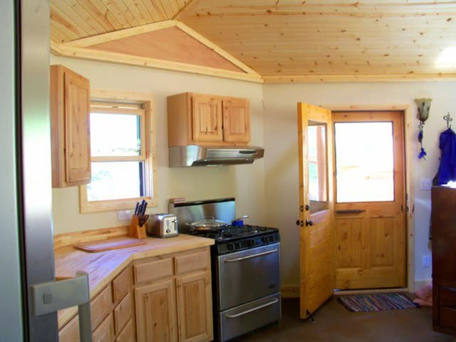 """A view of the entrance door with the full kitchen and walnut butcher block countertops. Kitchen features a 30"""" pro series four burner stove with oven, deep stainless steel sink, alder wood cabinets and a gorgeous Lieberrh refrigerator."""
