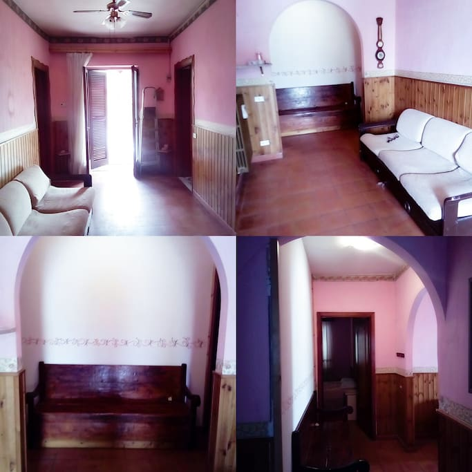 Salone con baule,arco,divano,eporta di ingresso dal balcone.
