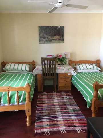 Main room room with 2 clean and comfortable single beds and desk