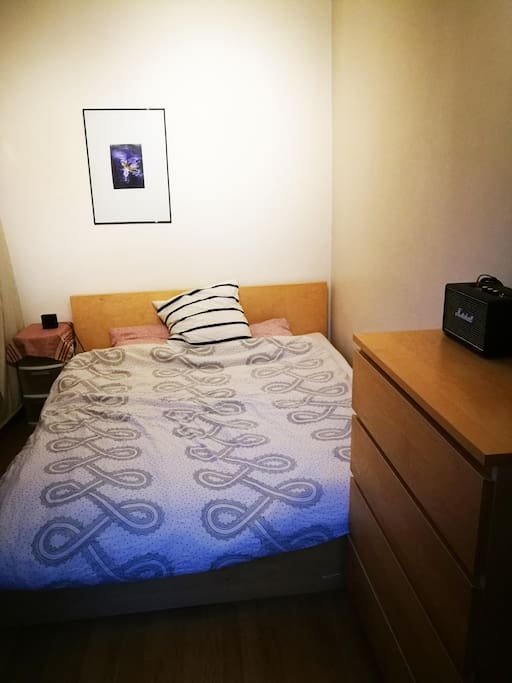 Bedroom with queen sized bed, wardrobe and cupboard.