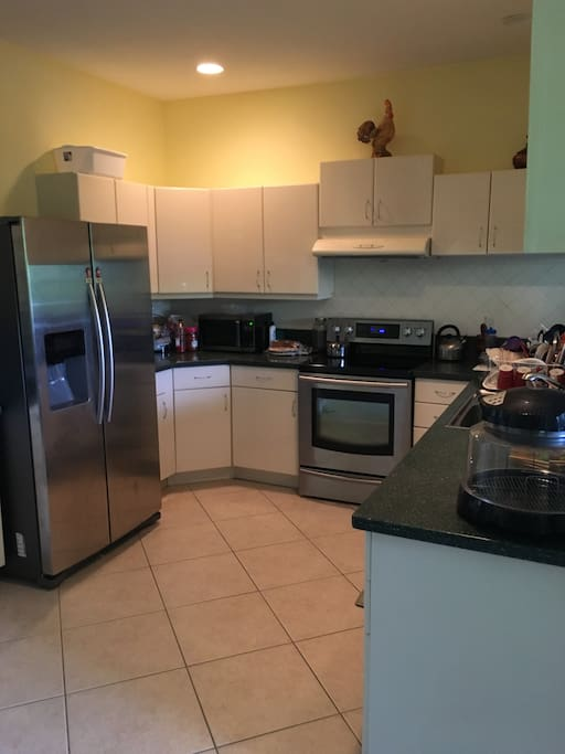 Kitchen including refrigerator, microwave, oven, stove, cooking space and cabinets.
