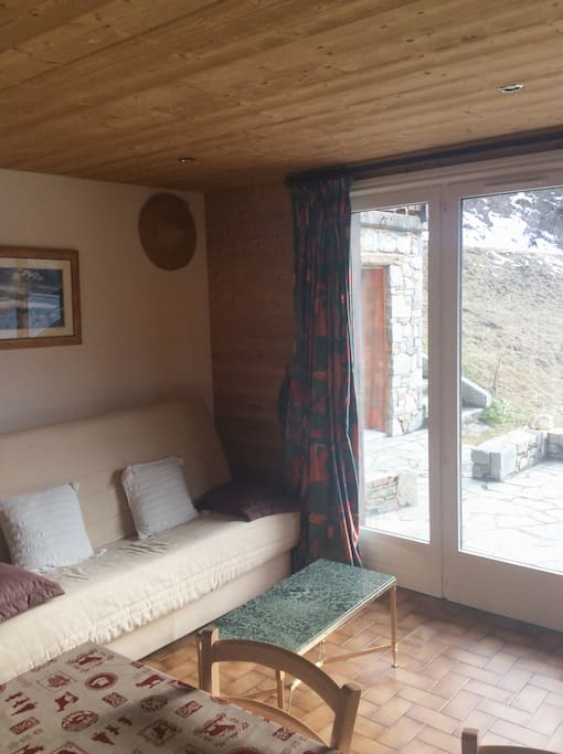 Canapé lit de type clic clac avec baie vitree donnant sur terasse
