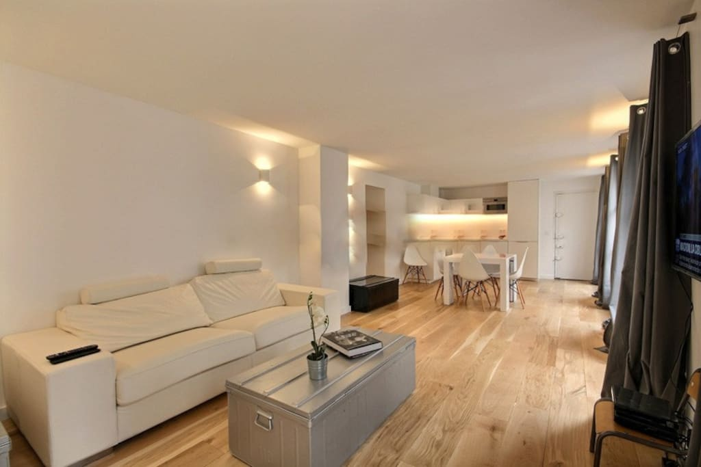 Living   The 35 square meters living room has 4 double glazed windows facing street . It is equipped with : folding dining table up to 6 people, sofa, coffee table, TV, hard wood floor.