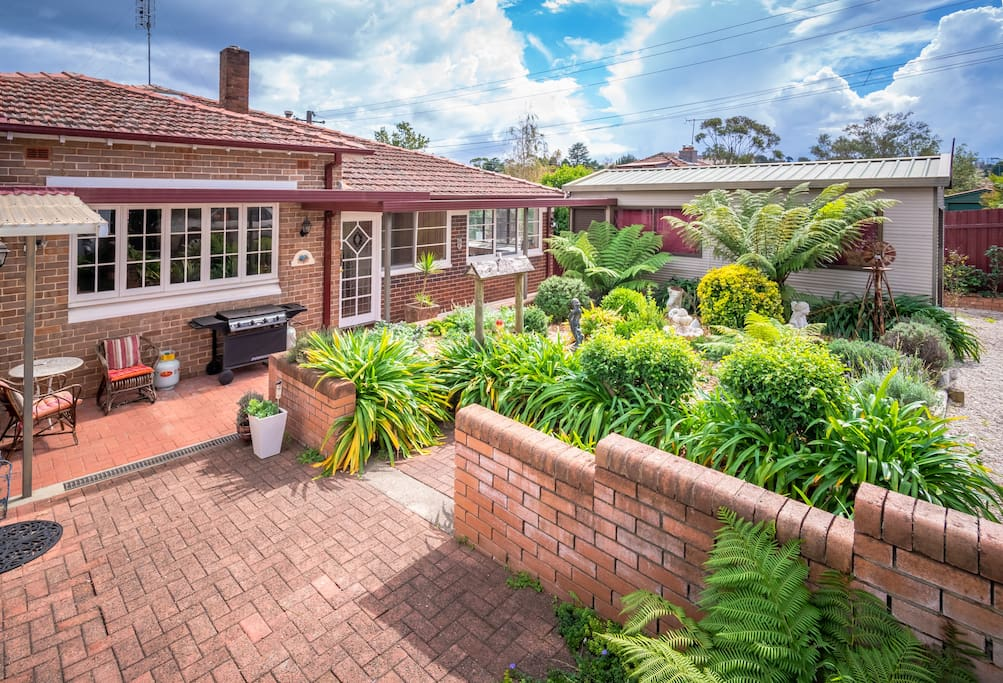 Sun drenched cottage garden and backyard, including outdoor BBQ and herb garden