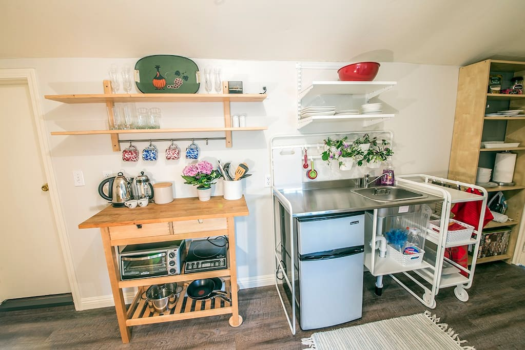 kitchenette with service for 4, sink, fridge, microwave, toaster oven, electric kettle, french press, induction plate, and pans