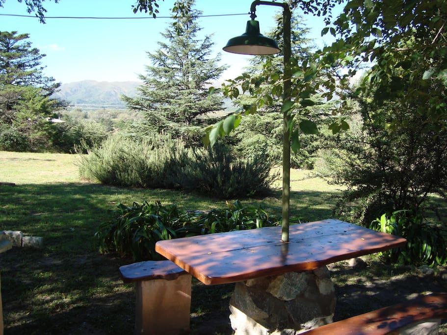 asadores con mesa y bancos bajo los arboles
