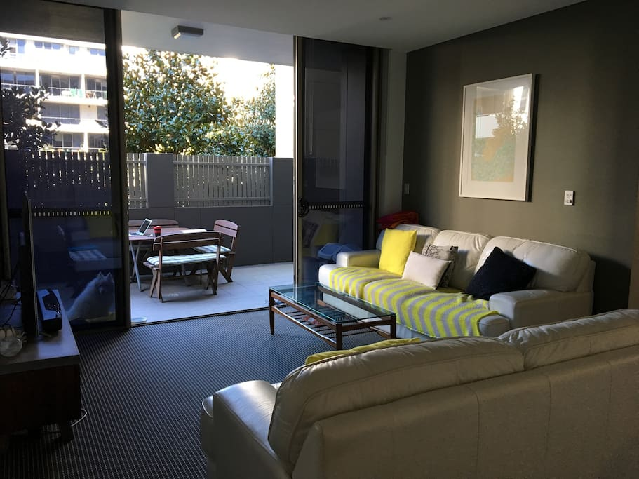 Spacious living area with seating for at least 5 adults. Opens to large ground floor courtyard