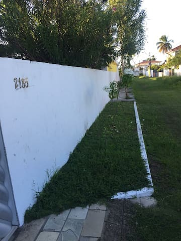 Rua, Calçada, Muro com número da casa, rampa de entrada da garagem da frente.