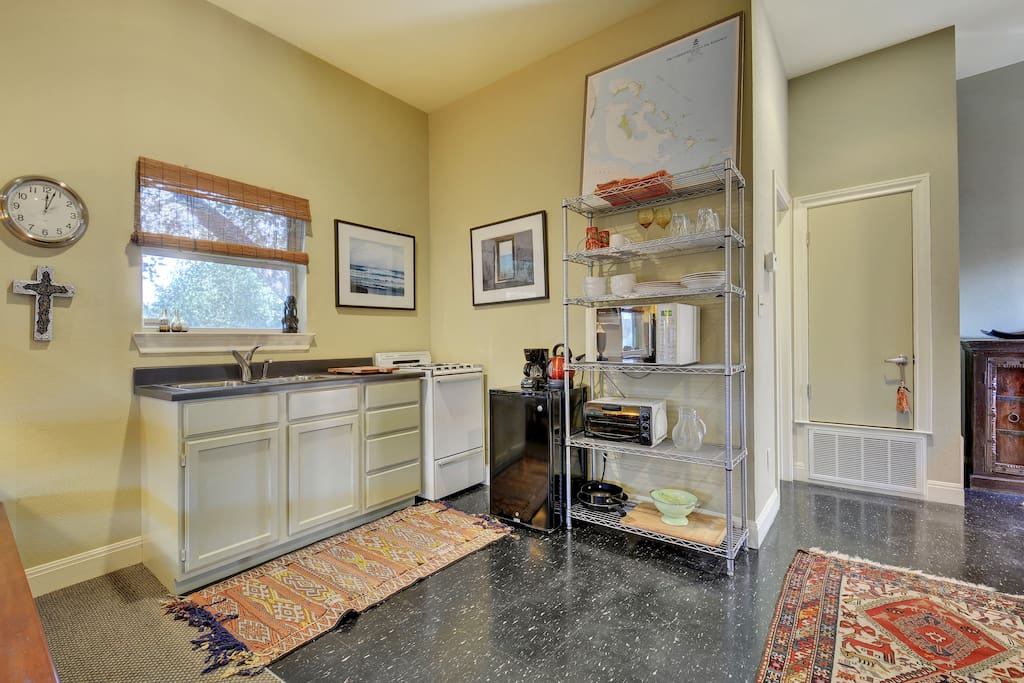 Small but mighty kitchenette in the studio with a sink, small fridge, and stove.