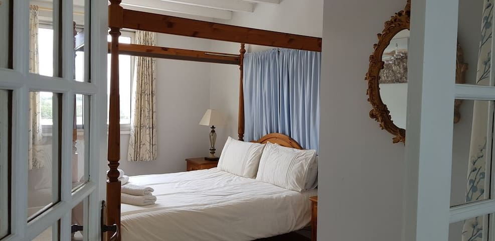 Bedroom 3 Four Poster Kingsize bed. Accessed through French doors from lower hall seating area. Views of pool and garden from window.