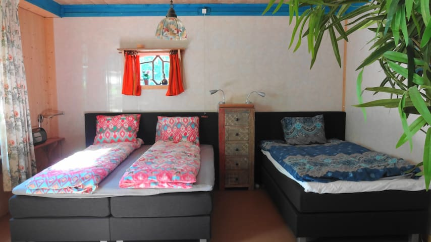 Slaapkamer1 met twee boxsprings, computertafel met twee stoelen en kasten.