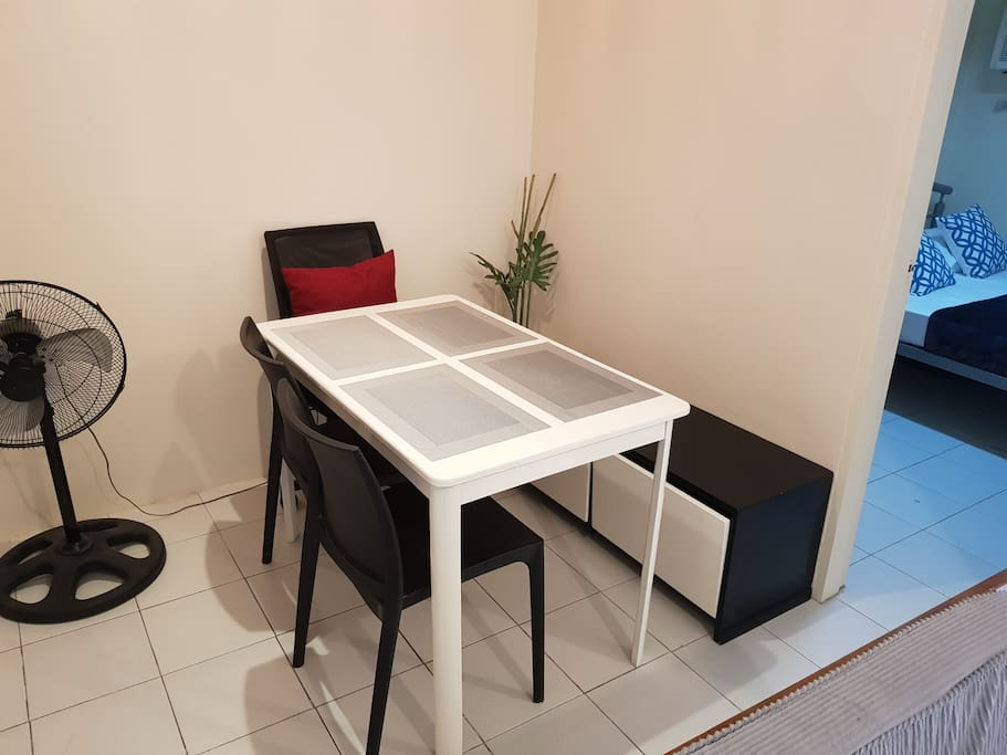 Dining area with bench, 2 chairs and computer chair beside the entrance to the bedroom