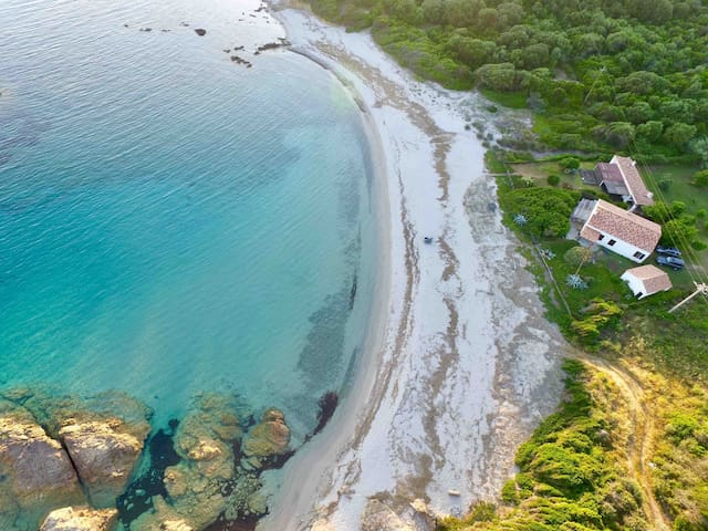 Maison dans une crique, sur une plage de sable