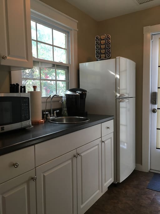 Kitchenette contains a sink, microwave, full size fridge, and Keurig