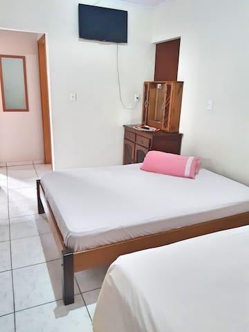 Quarto B possui 2 camas de casal, televisão.
