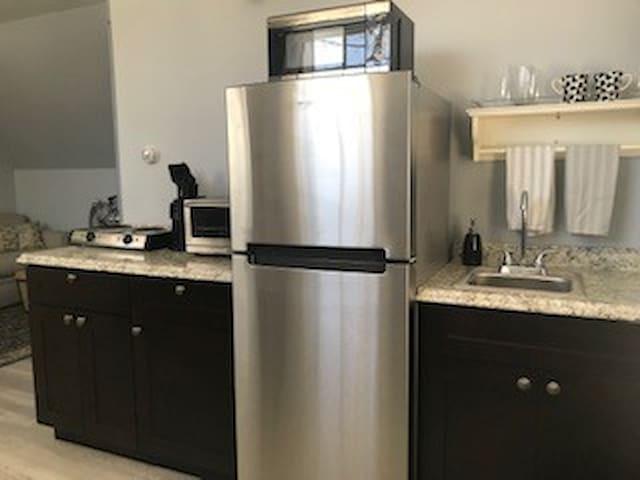 Efficient kitchen: microwave, 2 burner range top, convection oven,  Keurig, pots & pans, and baking dishes.