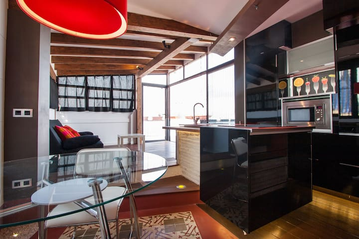 Kitchen area with fridge, microwave, sink, washing machine, table and chairs/Área de cocina con nevera, microondas, fregadero, lavadora, mesa y sillas
