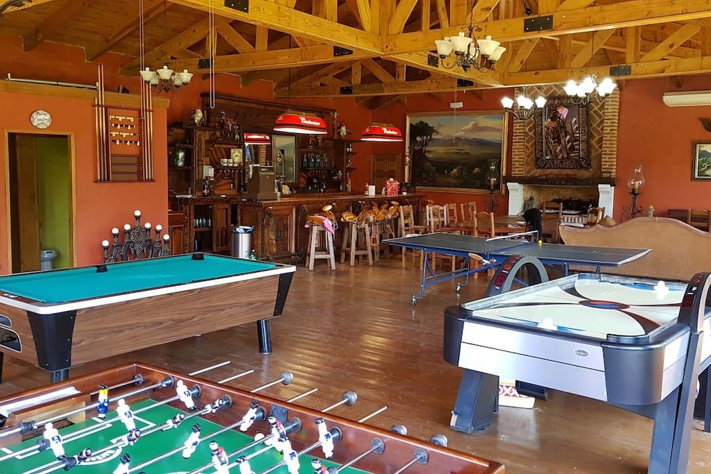 Salon de juegos con pantalla, mesa de billar, ping pong y futbolito