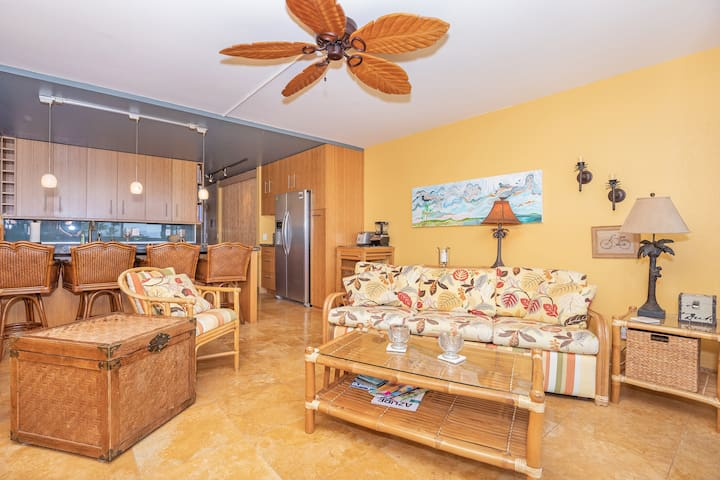 Living area features cozy sofabed, comfy chairs, ceiling fan, air conditioner, and tiki-inspired furnishings throughout.  Kitchen area feature bar seating for four.