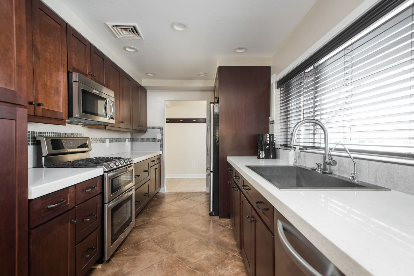 Fully equipped and newly renovated kitchen with stainless steel appliances and quartz countertops.